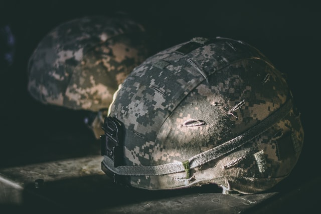 dimly lit modern military helmets on table