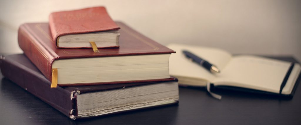stock photo: close-up shot of a stacked leather books & an open journal on a wooden desk